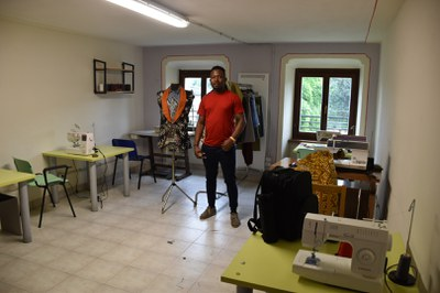 Der junge Ghanese näht Kleidungsstück